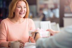 Положительные женщины сидя на таблице Стоковое Фото
