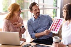 Положительные коллеги выбирая цвета Стоковая Фотография