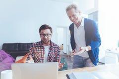 Положительные коллеги используя компьтер-книжку в офисе Стоковое Изображение