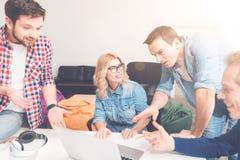 Положительные коллеги используя компьтер-книжку в офисе Стоковые Фотографии RF