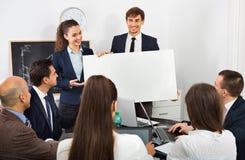 Положительные коллеги обсуждая план новой разработки Стоковые Изображения