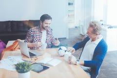 Положительные коллеги отдыхая в офисе Стоковые Изображения