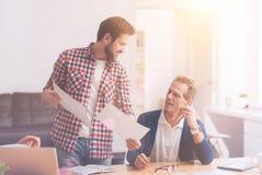 Положительные коллеги помогая одину другого в офисе Стоковые Изображения