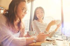 Положительные молодые женщины используя умный телефон в кафе Стоковое Фото