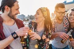 Положительные молодые человеки и женщины празднуя событие совместно Стоковые Изображения