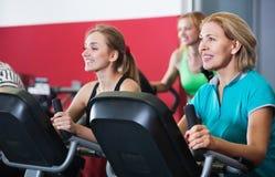 Положительные пожилые люди и молодые женщины разрабатывая в спортзале Стоковые Фотографии RF