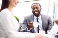 Положительные профессиональные коллеги сидя на таблице Стоковое Фото