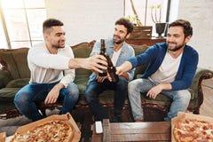 Положительные радостные люди поднимая пивные бутылки для здравицы Стоковая Фотография