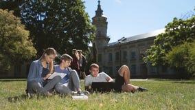 Положительные студенты колледжа изучая на лужайке кампуса видеоматериал