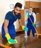 Положительные уборщики очищая и пылясь в доме Стоковое фото RF