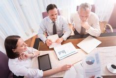 Положительные усмехаясь коллеги сидя на таблице Стоковая Фотография