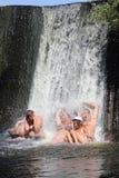 Положительные эмоции пока купающ в водопаде стоковое изображение