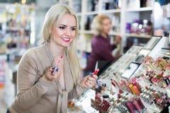 Положительный женский клиент покупая красную губную помаду в разделе состава Стоковая Фотография RF