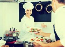 Положительный кашевар женщины давая салат к официантке Стоковые Изображения