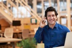 Положительный молодой бизнесмен крепко на работе в современном офисе Стоковые Фотографии RF