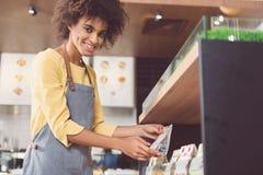 Положительный очаровательный продавец работает в магазине и выражает счастье Стоковое Изображение