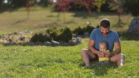 Положительный папа играя с милым младенческим мальчиком на траве видеоматериал