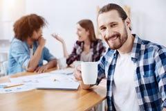 Положительный парень наслаждаясь кофе во время его перерыв на ланч Стоковые Изображения