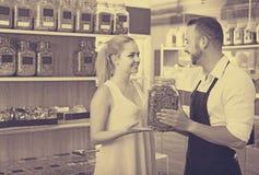 Положительный продавец человека держа стекло может с травами Стоковое Фото