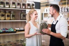Положительный продавец человека держа стекло может с травами Стоковое Изображение