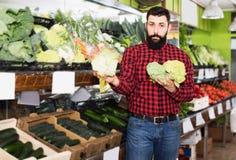 Положительный продавец человека показывая цветные капусты Стоковое Изображение
