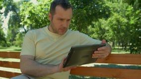 Положительный человек сидя в парке с компьтер-книжкой акции видеоматериалы