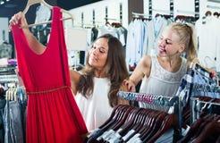 2 положительных девушки выбирая платье совместно Стоковые Фото