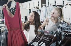 2 положительных девушки выбирая платье совместно Стоковая Фотография RF