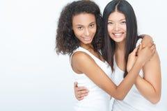 2 положительных девушки обнимая плотно Стоковое Изображение