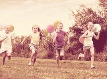 4 положительных дет бежать на зеленой лужайке Стоковое фото RF