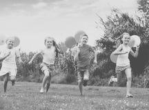 4 положительных дет бежать на зеленой лужайке Стоковая Фотография