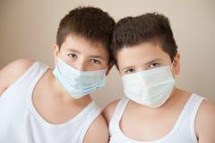 2 положительных мальчика в медицинских масках Стоковые Фото