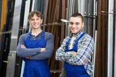 2 положительных работника представляя в магазине PVC Стоковые Фото