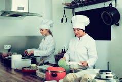 2 положительных шеф-повара женщин варя еду на кухне Стоковое Фото