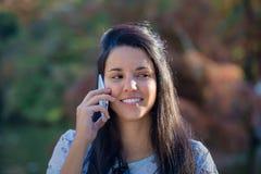 Подозрительная молодая женщина говоря на ее мобильном телефоне в парке Стоковое Изображение RF