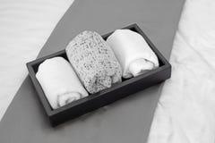 Полотенца в черном подносе на кровати Стоковые Изображения