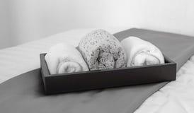 Полотенца в черном подносе на кровати Стоковые Изображения RF