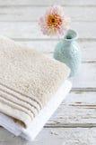 2 полотенца и одиночного цветок на деревянной предпосылке Стоковое Изображение RF