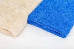 2 полотенца кладя на белую деревянную предпосылку Стоковые Фото