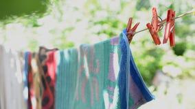 Полотенца отбрасывая и вися в солнце с bokeh сток-видео