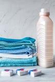 Полотенца складывают с детержентными и пластичными бутылками в прачечной Стоковое Фото