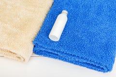 2 полотенца с одной меньшей бутылкой шампуня на белизне деревянной Стоковая Фотография