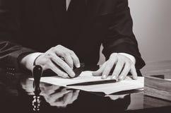 Подписывая подряд Юрист или notar на его рабочем месте Стоковая Фотография RF