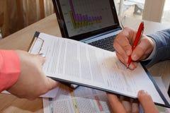 Подпись документов в офисе Бизнесмен сидя на столе, документах знака Документ на таблице, подписание документа, люди Стоковые Фотографии RF