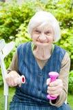 Подпитанная пожилая женщина делая тренировки с гантелями Стоковые Изображения RF