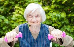 Подпитанная пожилая женщина делая тренировки с гантелями Стоковые Фото