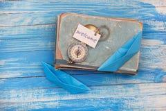 Подпишите гостеприимсво и компас на старой книге - винтажный стиль Стоковые Изображения