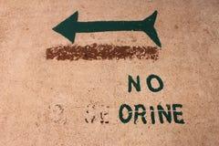 Подпишите которое говорит что 'не мочитесь' в испанском языке с зеленой стрелкой Стоковая Фотография RF