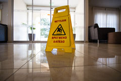 Подпишите показывать предупреждение пола предосторежения влажного на влажном плиточном поле в заходе солнца стоковые изображения