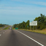 Подпишите сбоку дороги с ДОМАШНИМ СЛЕДУЮЩИМ ВЫХОДОМ на его Стоковое Изображение